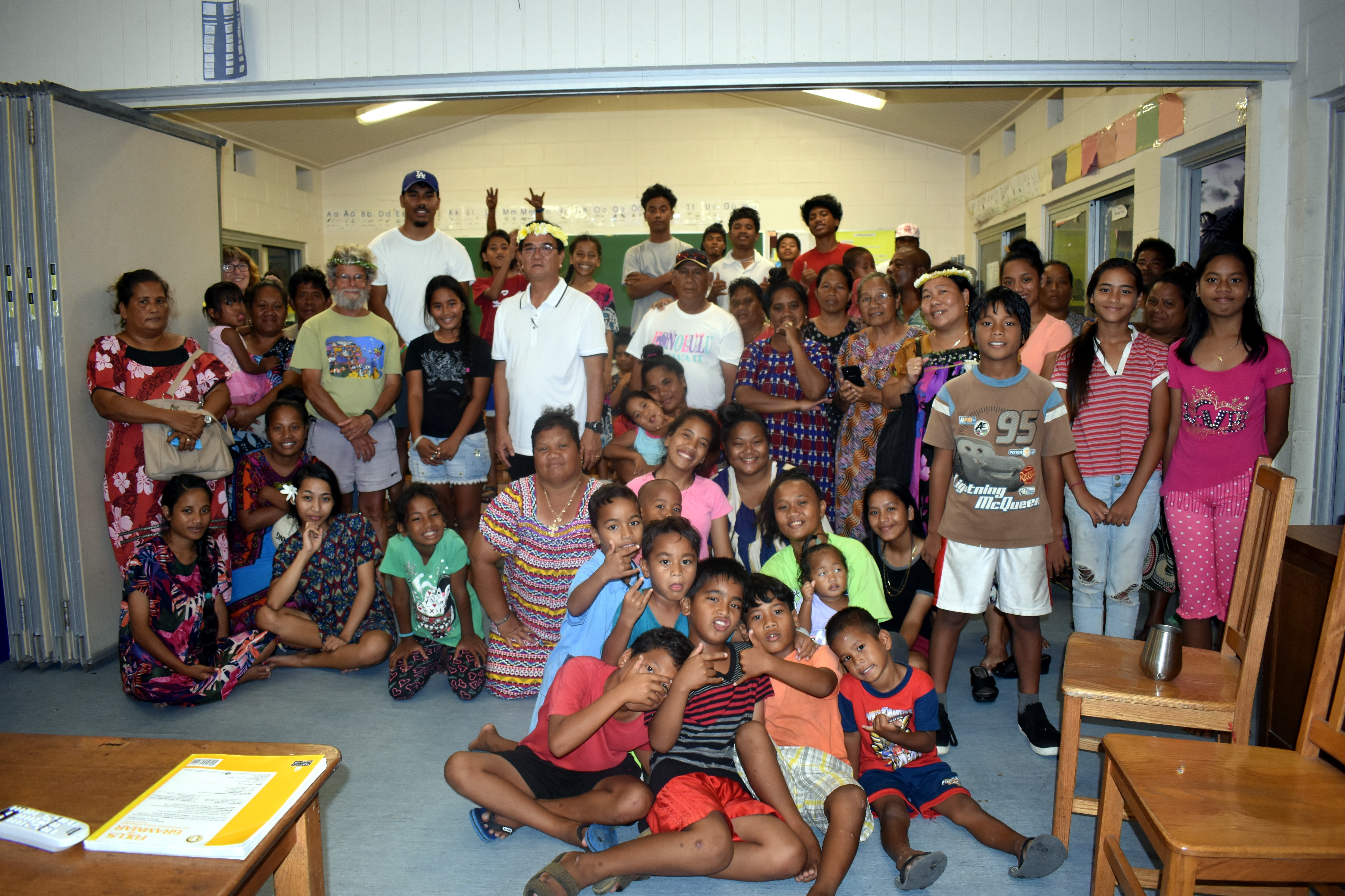 Several adults and children pose for an indoor group shot