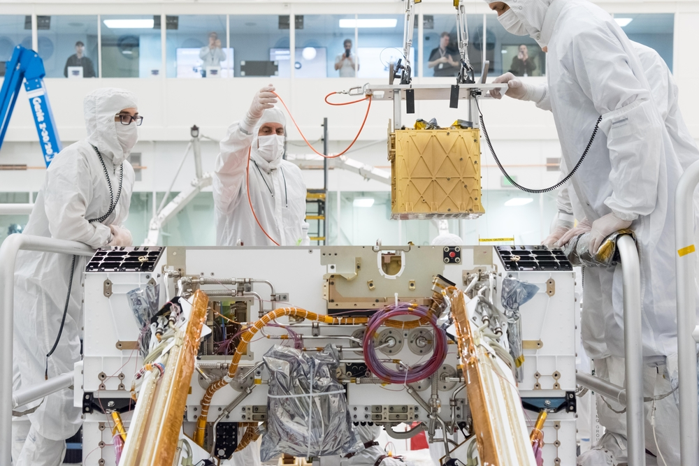 NASA technicians in a clean room install the MOXIE device in the Mars Rover