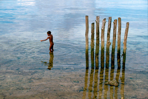 A young boy fishes with a pointed stick near a row of wooden pilings on Biak Island, Schouten Islands, Indonesia.
