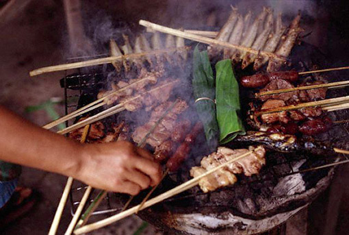 Various brochettes of meats, sausages, and fish being grilled on a charcoal brazier in Vientiane, Laos, August 1998 (© Owen Franken/CORBIS).