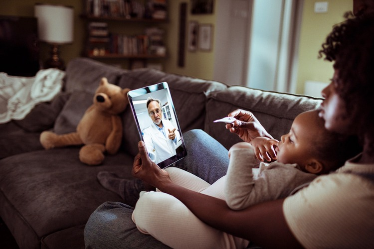 Stock image: a woman holding a baby and a thermometer consults a doctor on a tablet