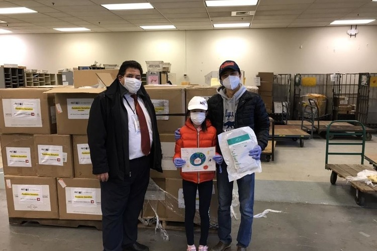 Three people with masks on standing in front of boxes