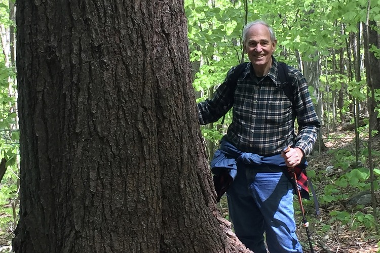 In hiking clothes, Bill Moomaw stands beside a tree trunk in the forest