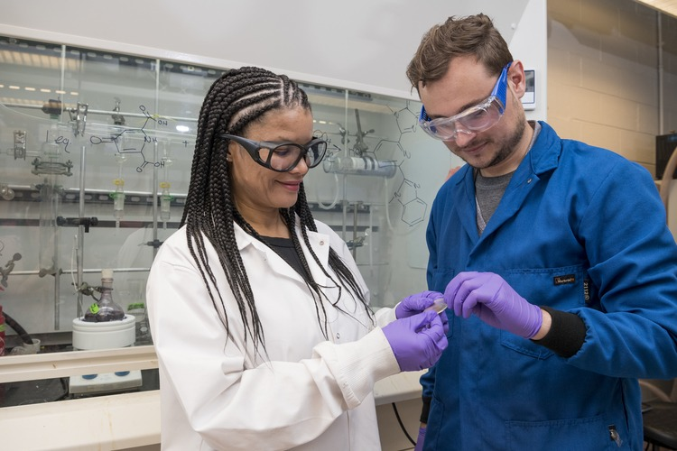 Woman in lab with gloves and lab coat holding object with man in lab