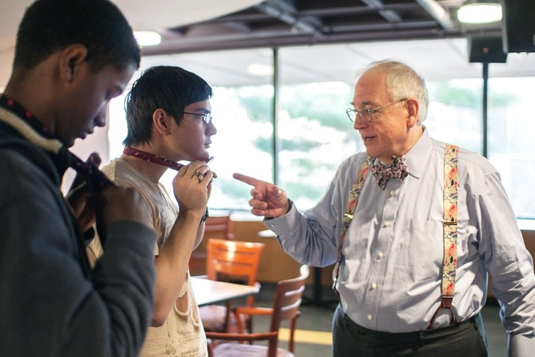 MIT alum teaches a student how to tie a bowtie