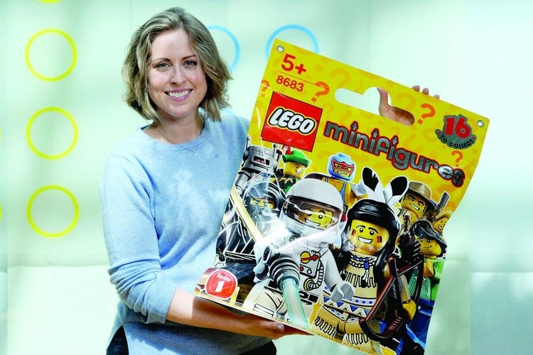 Tara Wike '97, design lead for Lego Minifigures, holds an oversized product replica.