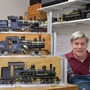 Ed Hume, dressed in overalls, sits next to a three-level display of model trains in his workshop, with another displayed on a shelf on the wall behind him.