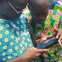 Cocoa farmers in western Africa look at mobile device