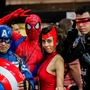Four people pose in Marvel superhero costumes